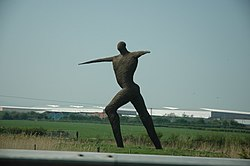 Large statue of a human figure with arms outstretched