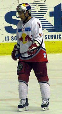 An ice hockey player standing, looking to the left of the camera. He is wearing a blue helmet and a red and white uniform.
