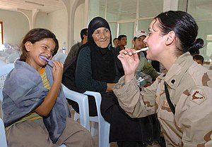 Spc. Elizabeth Jarry shows an Iraqi girl prope...