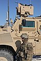U.S. Army Spc. Kristen Overby, with the 1st Platoon, 527th Military Police Company, 709th Military Police Battalion, 18th Military Police Brigade, stands next to a mine-resistant, ambush-protected vehicle at 120128-A-BZ540-013.jpg