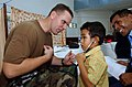 US Navy 050329-N-6665R-086 Lt. Cmdr. Jeffrey W. Bledsoe, a U.S. Navy nurse assigned to the Military Sealift Command (MSC) hospital ship USNS Mercy (T-AH 19), entertains a Dili child with his stethoscope.jpg