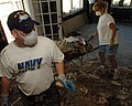 US Navy 051017-N-3729H-062 Draftsman 2nd Class Robert Smith, a volunteer Sailor assigned to the Nimitz-class aircraft carrier USS John C. Stennis (CVN 74), along with his mother, Cindy Stumpf, remove debris from their house.jpg