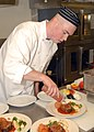 US Navy 070907-N-7656R-002 Culinary Specialist 2nd Class Sean Corcoran, assigned to Naval Station Everett Galley, puts the final touches on meatloaf during a culinary arts competition.jpg