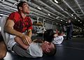 US Navy 080905-N-8534H-003 Electronics Technician 3rd Class Khristopher Gonzalez displays his offensive ground game to Ship's Serviceman Seaman Brandon Benjamin during a mixed-martial arts training session aboard the aircraft c.jpg