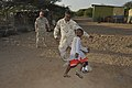 US Navy 091112-N-3417F-003 Petty Officer 2nd Class Jojuan James, right, and Petty Officer 2nd Class Chris Schoene play soccer with a boy from a small village outside Camp Lemonnier.jpg