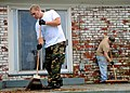 US Navy 091118-N-9116H-009 Fire Controlman 2nd Class Andrew Miller and Interior Communications Electrician 2nd Class Michael Wiseman sweeps debris from a porch during a city of Hampton sponsored community outreach.jpg