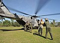 US Navy 100203-N-6214F-075 Col. Dan Stoltz, commander of the Joint Forces Special Operations Component Command-Forward, and air crewmen from an MH-53E Sea Dragon helicopter unload cots at a medical clinic.jpg