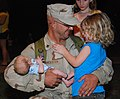 US Navy 100719-N-7084M-753 Construction Mechanic 2nd Class Robert Lancaster is welcomed home by his family after returning from a four-month deployment.jpg