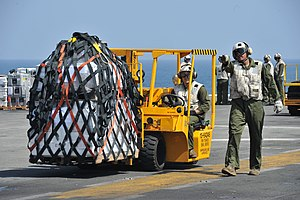 US Navy 120116-N-KD852-039 Marines from Combat Cargo assigned to 11th Marine Expeditionary Unit (11th MEU) move supplies across the flight deck abo.jpg