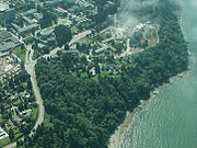 View of the north part of the Point Grey Campus, including Green College, the Chan Centre for the Performing Arts, and the Museum of Anthropology. The Grand Campus Washout of 1935 carved a ravine from the area at the top left corner, diagonally through the wooded gully, to the beach.
