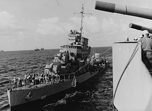 "The USS Rowan receiving provisions via ""high-line"" from USS Augusta (CA-31) while operating at sea, 4 December 1942."
