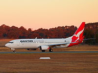 A Qantas Boeing 737 taking off at sunset