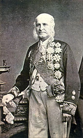 A tintype photograph showing an older, white-haired man standing in formal dress with a sash of office and a cutaway coat with embroidered sleeves which is covered in medals