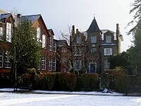 A colour photograph of an unusual Victorian house with a small spire on the top. To the left is a set of old-fashioned schoolrooms with large sash windows. In front of the house is a small lawn, covered in snow.