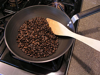 Home roasting coffee - Roasting coffee beans in a wok on a kitchen stovetop
