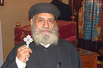 Coptic cross - Coptic priest holding a hand-held blessing cross (Cairo 2010).
