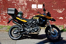 Black and yellow BMW F800GS with topbox and motorcycle helmet on the seat, parked in front of a brick wall covered in peeling red paint