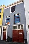 Huis met gepleisterde lijstgevel. Nok evenwijdig aan de straat. Voordeuromlijsting en toegang tot bedrijfsruimte