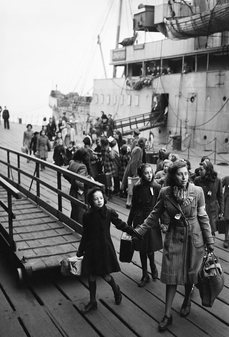 A Dutch school teacher leads a group of refugee children just disembarked from a ship at Tilbury Docks in Essex during 1945. D24064