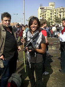 A female protester with her camera and a flower.jpg