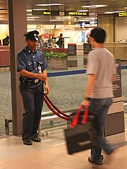 An Aetos auxiliary police officer controlling access to the runway side of the Departure Hall at Terminal 1, Singapore Changi Airport. Such services are now provided by Certis CISCO.
