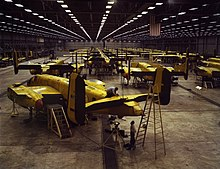 Interior of huge aircraft factory where rows of bombers are being assembled
