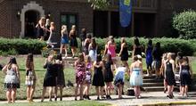 Több tucat hétköznapi ruhás nő sorakozik a lépcsőn a gyepen keresztül az egyházi ház (Alpha Xi Delta) előtt.