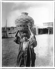 Apache Indian girl carrying an olla (a water basket) on her head, ca.1900 (CHS-2328).jpg