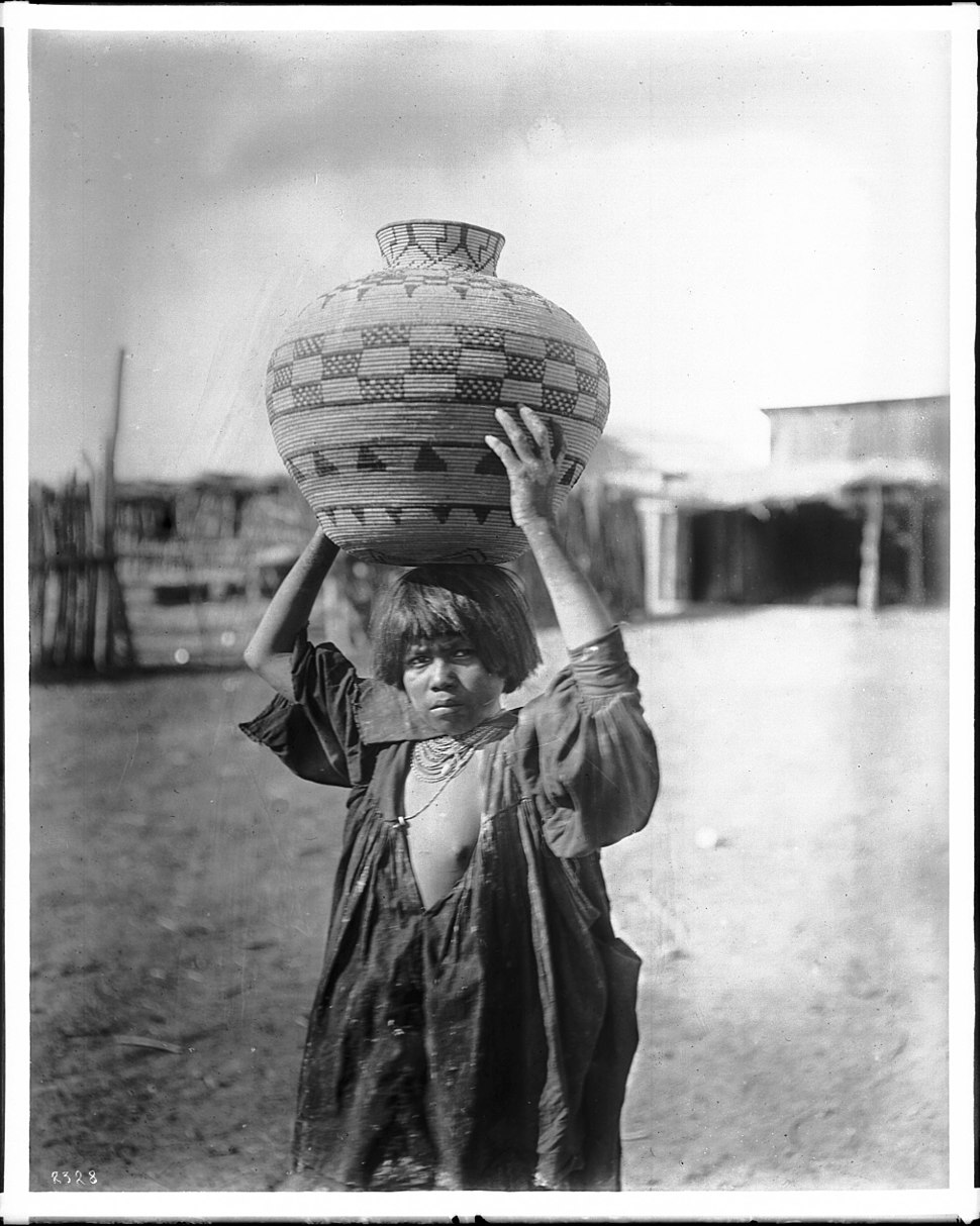 Apache Indian girl carrying an olla (a water basket) on her head, ca.1900 (CHS-2328)