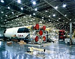 A large horizontal rocket with USA painted on the side inside of a manufacturing facility