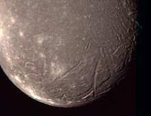 the bottom hemisphere of Ariel is seen, reddish and dark, with cracks and craters lining the edge