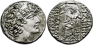 Photograph of of a Roman coin struck in imitation of the coins of Philip I Philadelphus of Syria, depicting Philadelphus in left-facing profile on the obverse and sitting in his throne on the reverse