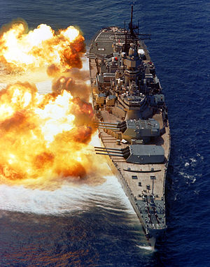 USS Iowa in her post 1980s rebuild. The battleship is pointed toward the viewer, with her 9 gun barrels pointed to the left for a gunnery exercise. Fire can be seen erupting from the gun barrels, and a concussive effect is visible on the water.