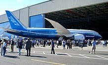 The Everett Factory Hall's huge door opens as the first 787 is rolled out. Surrounding the aircraft are guests and the public.