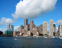 Skyline of a waterfront city. Several skyscrapers are visible in the distance, the tallest being a building with rounded edges and a red facade at the center of the image. To the extreme right is a white clock tower that appears shorter than most of the other tall buildings; two concrete, Brutalist-era apartment buildings are adjacent to the clock tower.