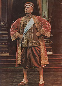 Man in ornate Asian garb stands with fists planted on his hips