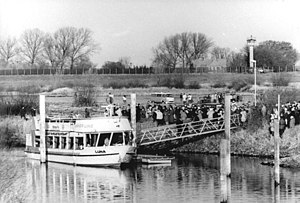 Amt Neuhaus - First ferry crossing the reopened border in the Elbe river on 16 November 1989 with East German border fences and watch towers in the background.