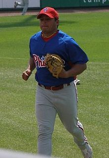 A man in a blue baseball jersey, white baseball pants with red pinstripes, and a red baseball cap jogs across the baseball field wearing a tan catcher's mitt on his left hand.