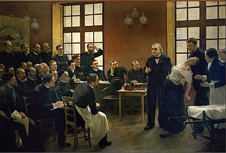 A painting of a 19th-century medical lecture. At the front of the class, a woman faints into the arms of a man standing behind her, as another woman, apparently a nurse, reaches to help. An older man, the professor, stands beside her and gestures as if making a point. Two dozen male students watch them.