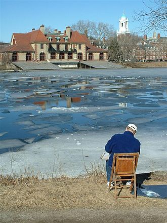 Cambridge, Massachusetts - A view from Boston of Harvard's Weld Boathouse and Cambridge in winter. The Charles River is in the foreground.
