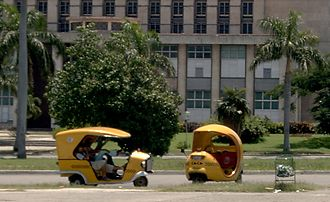 "Tourism in Cuba - ""Cocotaxis"" in Plaza de la Revolución, Havana. Because of the rapid growth of tourism in Cuba, taxi drivers can earn more than lawyers and doctors."