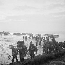 Men in the foreground burdened with equipment, behind them are mud or sand flats and in the distance landing craft