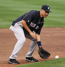 "A man in a blue baseball uniform with ""New York"" written on the front in grey letters and a navy hat with white letters ""N"" and ""Y"" interlocking prepares to catch a ground ball with his baseball glove."
