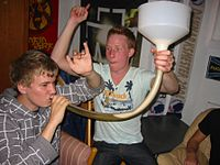 One person holds a clear pipe to their mouth, while a second holds the other end of the pipe with a large white plastic funnel attached.  The pipe is part-filled with a translucent yellow-brown liquid, with the remainder of the pipe and the bottom of the funnel filled with a foamy head.