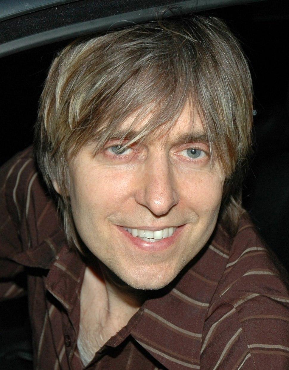 Head shot of a man wearing a brown-striped shirt
