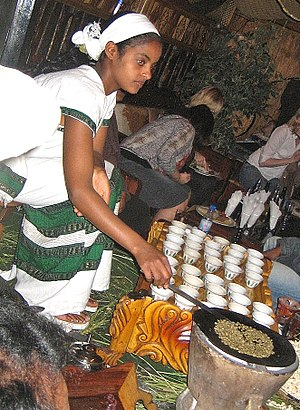 Culture of Africa - An Ethiopian woman preparing Ethiopian coffee at a traditional ceremony. She roasts, crushes and brews the coffee on the spot.
