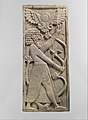 Furniture plaque carved in relief with a male figure grasping a tree; winged sun disc above MET DP110643.jpg