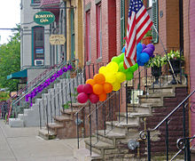 Stoops on some brick houses, seen looking along the sidewalk. One has balloons in the colors of the rainbow tied to its railing. Another has a purple ribbon.