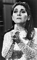 A black and white photograph of a caucasian woman with dark hair clasping her hands together.