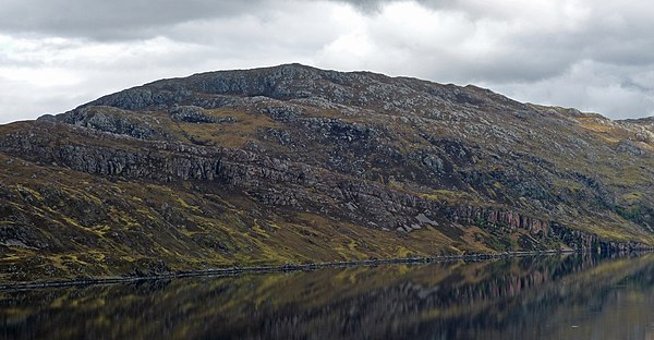 The Glencoul Thrust at Aird da Loch, Assynt in Scotland. The irregular grey mass of rock is formed of Archaean or Paleoproterozoic Lewisian gneisses thrust over well-bedded Cambrian quartzite, along the top of the younger unit. Glencoul Thrust Fault Zone in Scotland 2014.jpg